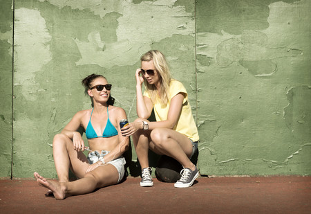 musically: Teenage girls sharing headphones