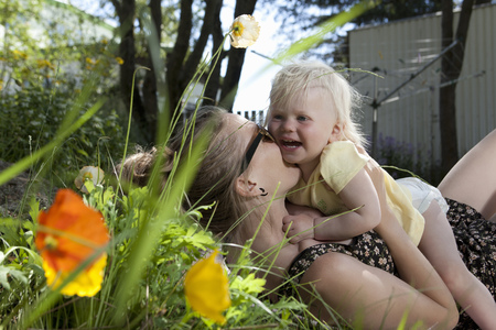 smooching: Mother and daughter playing outdoors LANG_EVOIMAGES