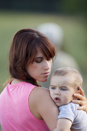 Mother holding crying baby outdoors
