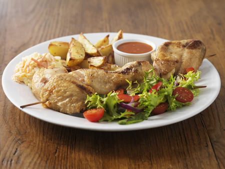 Plate of chicken with salad and potatoes