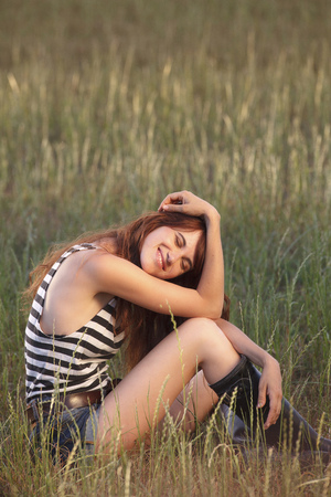 Woman sitting in grassy field LANG_EVOIMAGES