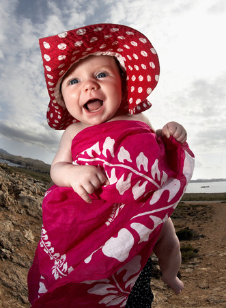 Infant laughing on beach LANG_EVOIMAGES