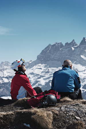 Skiers resting on rocky mountaintop
