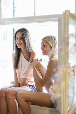 gratify: Smiling women sitting in windowsill