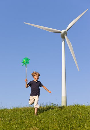 gratify: Boy with pinwheel by wind turbine LANG_EVOIMAGES