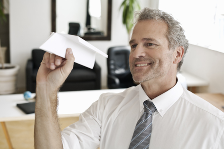 mischeif: Businessman playing with paper airplane LANG_EVOIMAGES