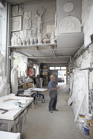 faiths: Worker standing in relief carving shop