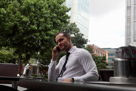 talker: Businessman on cell phone at cafe