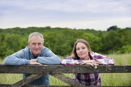 leaning by barrier: Father and daughter on wooden fence