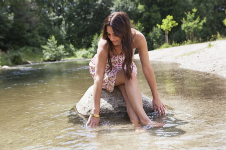 Teenage girl sitting on rock in stream LANG_EVOIMAGES