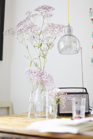 antique vase: Flowers,radio and water glass on table