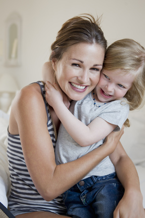 enthusiastically: Mother and daughter hugging on bed