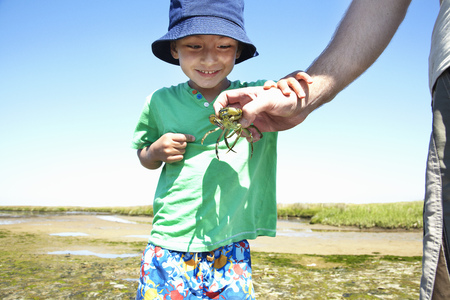 faiths: Boy examining crab in fathers hand
