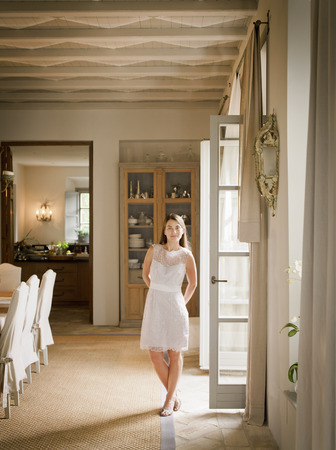 Woman standing in dining room LANG_EVOIMAGES