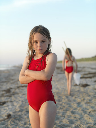 hardships: Girl standing on sandy beach