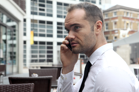 sidewalk talk: Businessman on cell phone at cafe