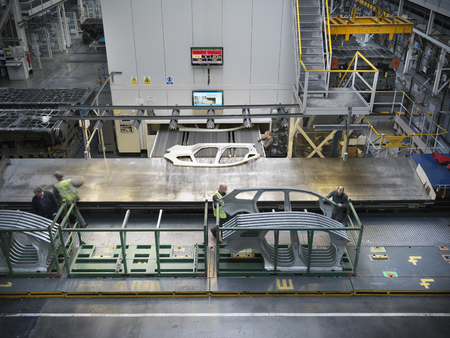 industrialization: High angle view of workers handling car parts as they come out of press in car factory LANG_EVOIMAGES