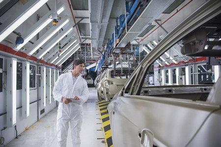 Worker inspecting car body in car factory LANG_EVOIMAGES