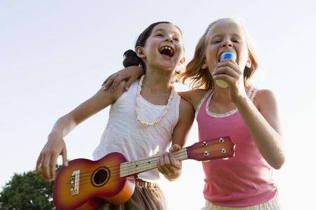 Girls singing together outdoors LANG_EVOIMAGES