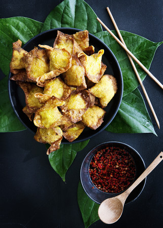 leafed: Plate of deep fried dumplings with sauce