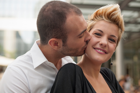 smooching: Smiling couple kissing outdoors