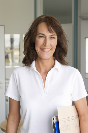 Smiling woman carrying papers indoors