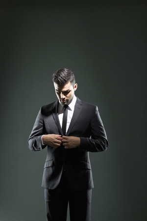 welldressed: Businessman buttoning suit jacket LANG_EVOIMAGES