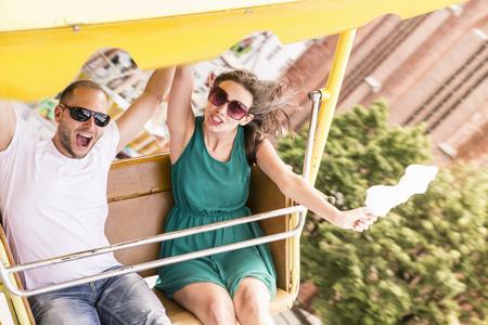 Couple riding amusement park ride LANG_EVOIMAGES