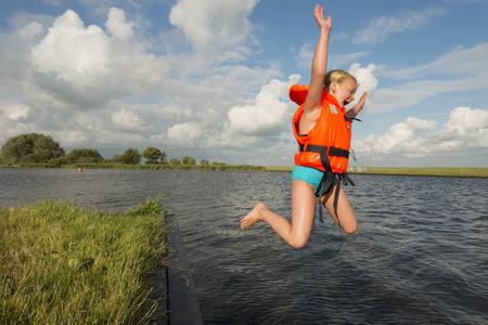 Girl jumping into rural lake LANG_EVOIMAGES