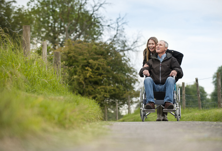 gratify: Woman pushing father in wheelchair