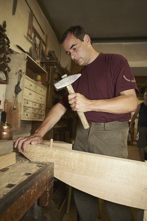 makes: Worker hammering nail into wood
