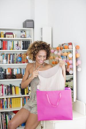 shopper: Smiling woman admiring new dress