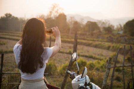 sight seeing: Woman on moped taking photograph in rural scene