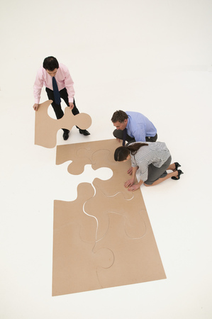 strategize: Business people assembling puzzle
