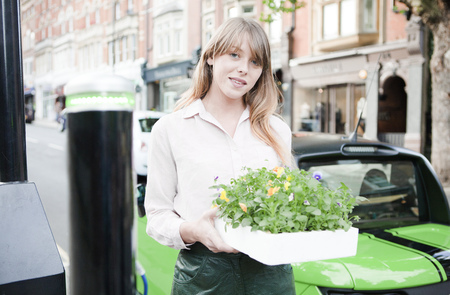 shopper: Woman carrying flowerbox on city street