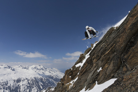 Snowboarder jumping on rocky slope LANG_EVOIMAGES