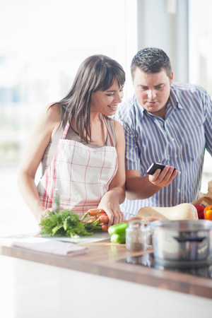 30 to 40 year olds: Couple looking at smartphone whilst preparing food