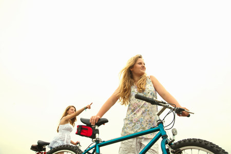 Girls with bikes,pointing LANG_EVOIMAGES