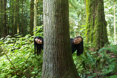 peep: Women peeking out from behind tree LANG_EVOIMAGES
