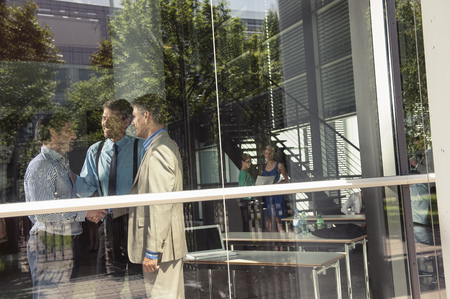 accomplishes: Businessmen shaking hands in office