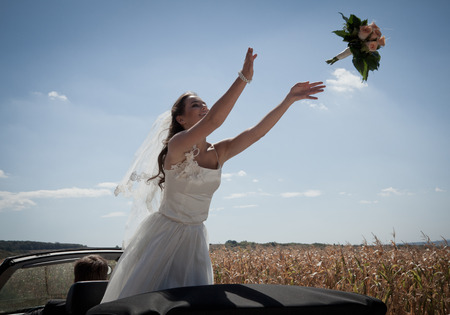 low spirited: Newlywed bride tossing bouquet from car LANG_EVOIMAGES