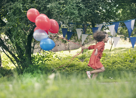 children party: Girl holding bunch of balloons outdoors LANG_EVOIMAGES