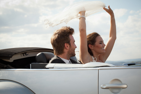 enthusiastically: Newlywed couple riding in convertible LANG_EVOIMAGES