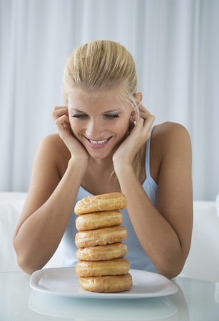 Woman admiring stack of donuts