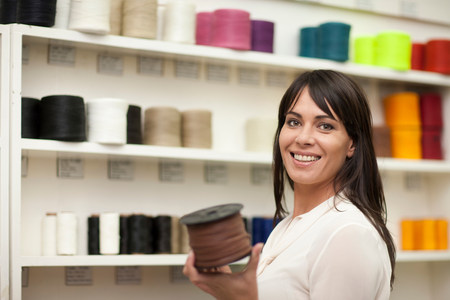 customer facing: Woman holding spool of thread LANG_EVOIMAGES