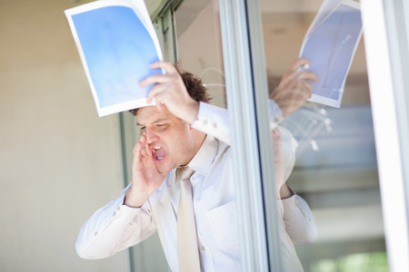aggressively: Businessman shouting from office window LANG_EVOIMAGES