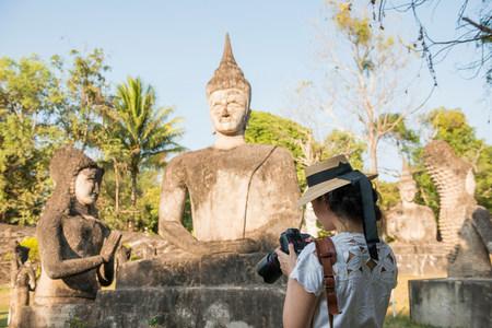 Woman photographing statue,Xieng Khu,Vientiane,Laos LANG_EVOIMAGES