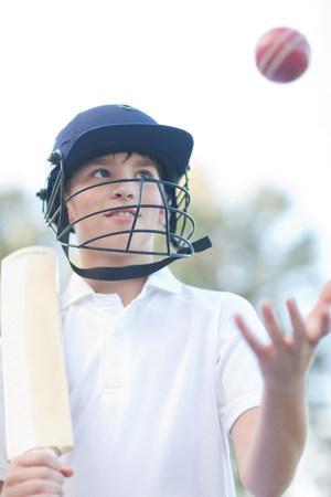 Boy wearing helmet catching cricket ball LANG_EVOIMAGES