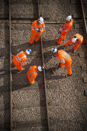hard: Railway workers examining train tracks