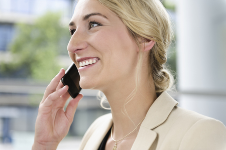 acknowledging: Businesswoman talking on cell phone LANG_EVOIMAGES